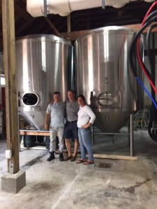 The Brewers and Susan in Front of tTheir Brand-New Fermenters